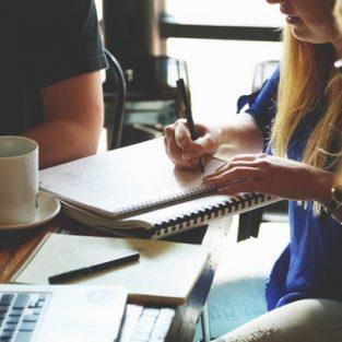 E-Learning workshop wordpress, afbeelding van cursisten aan tafel met laptops en studiemateriaal