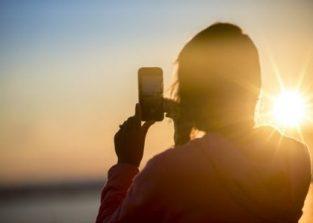 vrouw fotografeert ondergaande zon met smartphone